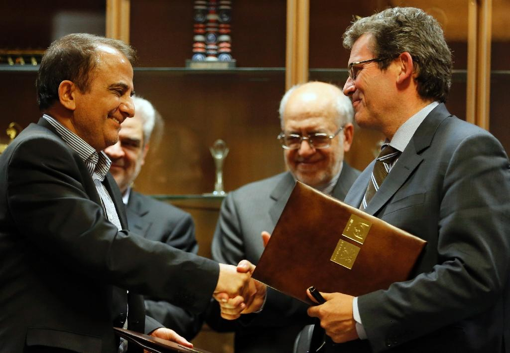 Jean-Christophe Quemard (right) of Peugeot Citroen (PSA) shakes hands with Iran Khodro's CEO Hashem Yekeh-Zareh in Tehran on June 21, 2016 (AFP Photo/Atta Kenare)