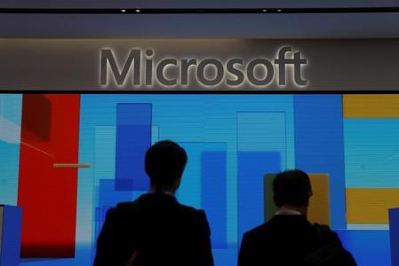 FILE PHOTO: Visitors stand in front of a display screen at Microsoft's new Oxford Circus store ahead of its opening in London