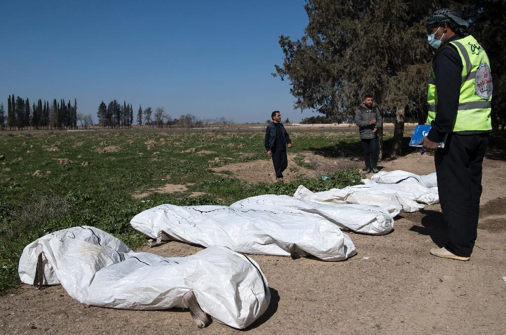 Workers gather bodies found in another mass grave near the northern Syrian city of Raqa on February 19, 2019