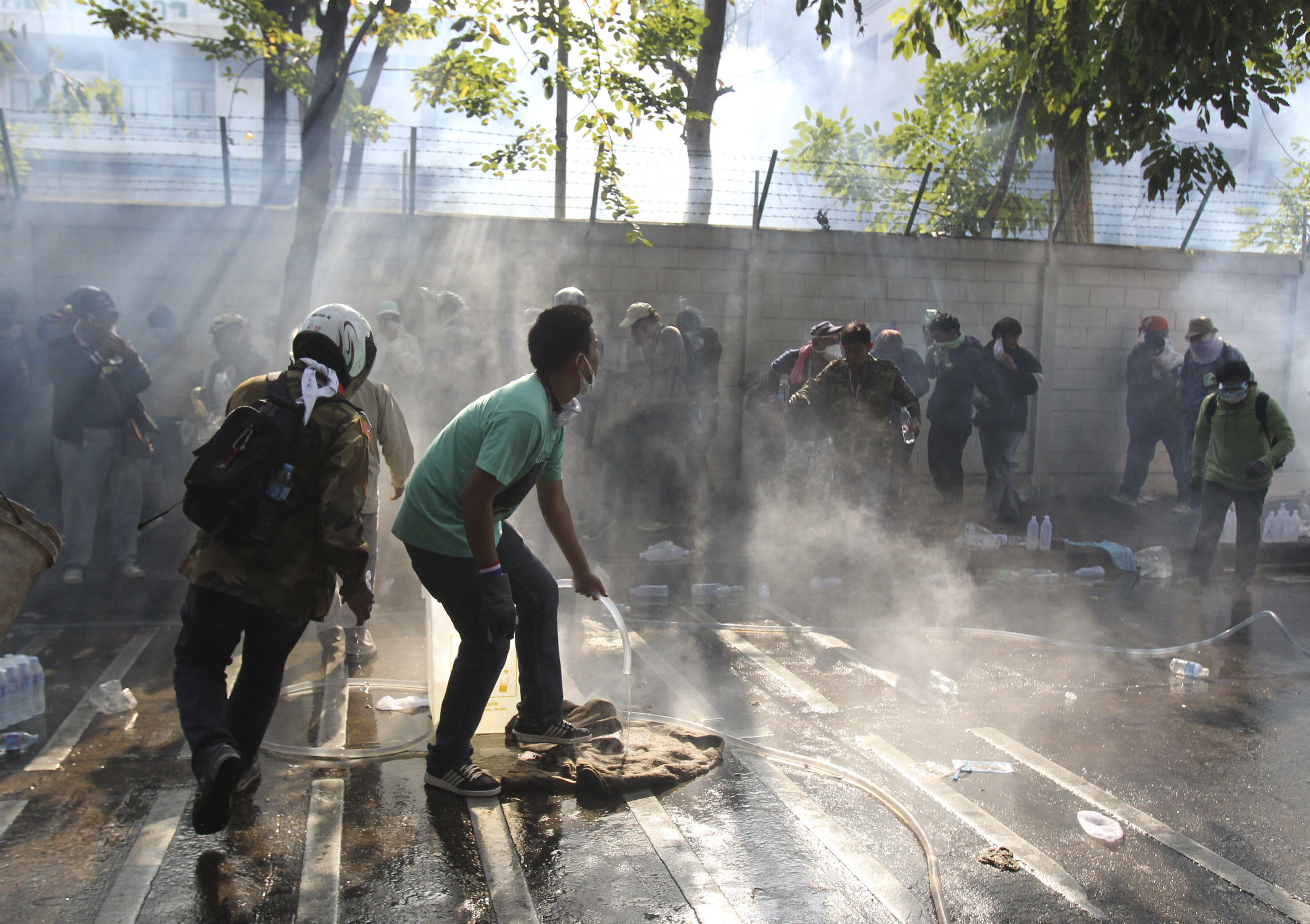 Anti-government protesters react to tear gas fired by riot police at a gymnasium in Bangkok, Thursday, Dec. 26, 2013. Officers fired tear gas and rubber bullets toward protesters trying to force their way into a sports stadium where candidates were gathering to draw lots for their position on polling papers. (AP Photo/Sakchai Lalit)