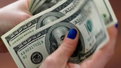 Dollar holds gains as investors cling to trade hopes