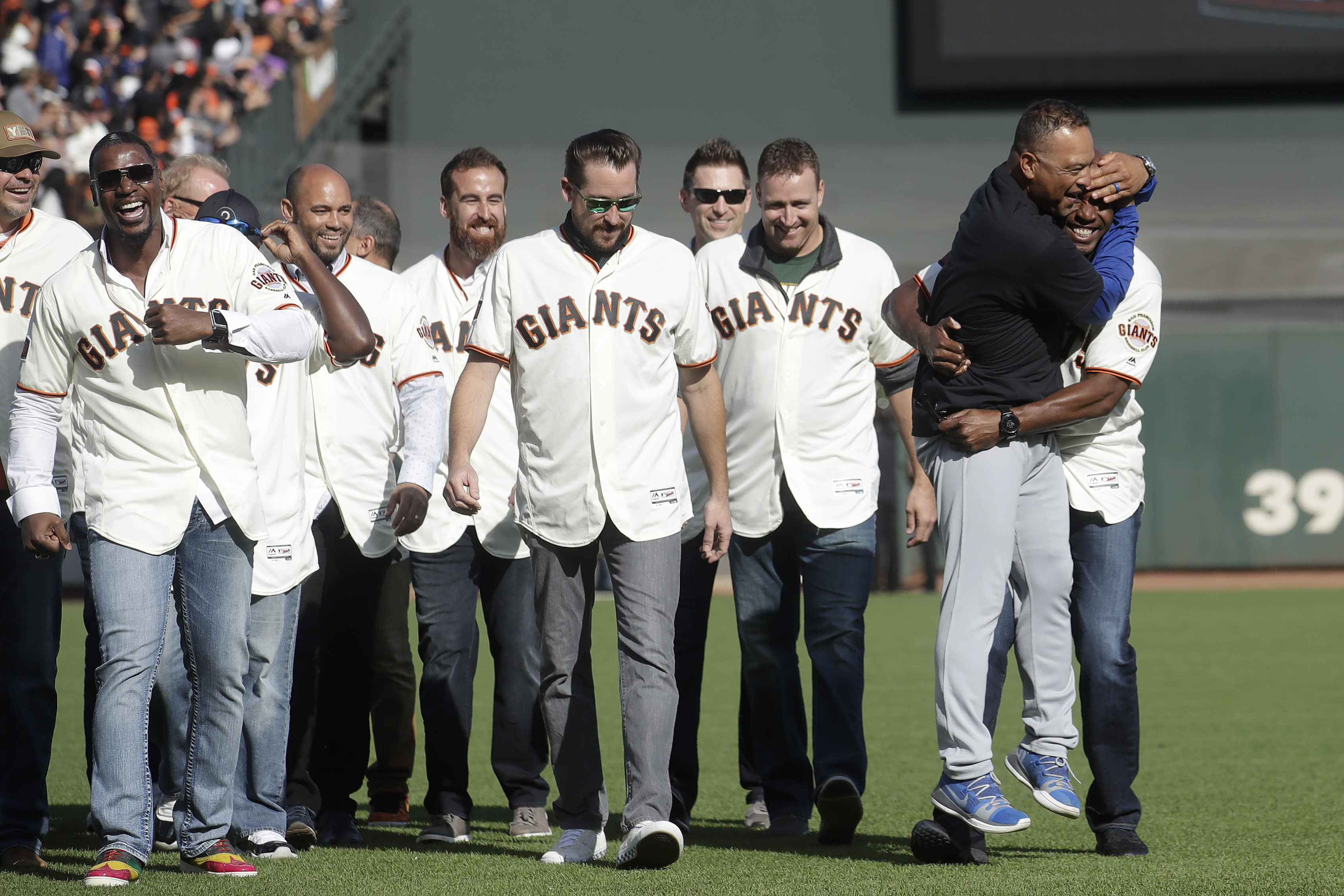 Los Angeles Dodgers manager Dave Roberts, second from left, hugs former San Francisco Giants player Barry Bonds during a ceremony honoring Giants manager Bruce Bochy after a baseball game between the Giants and the Dodgers in San Francisco, Sunday, Sept. 29, 2019. (AP Photo/Jeff Chiu, Pool)
