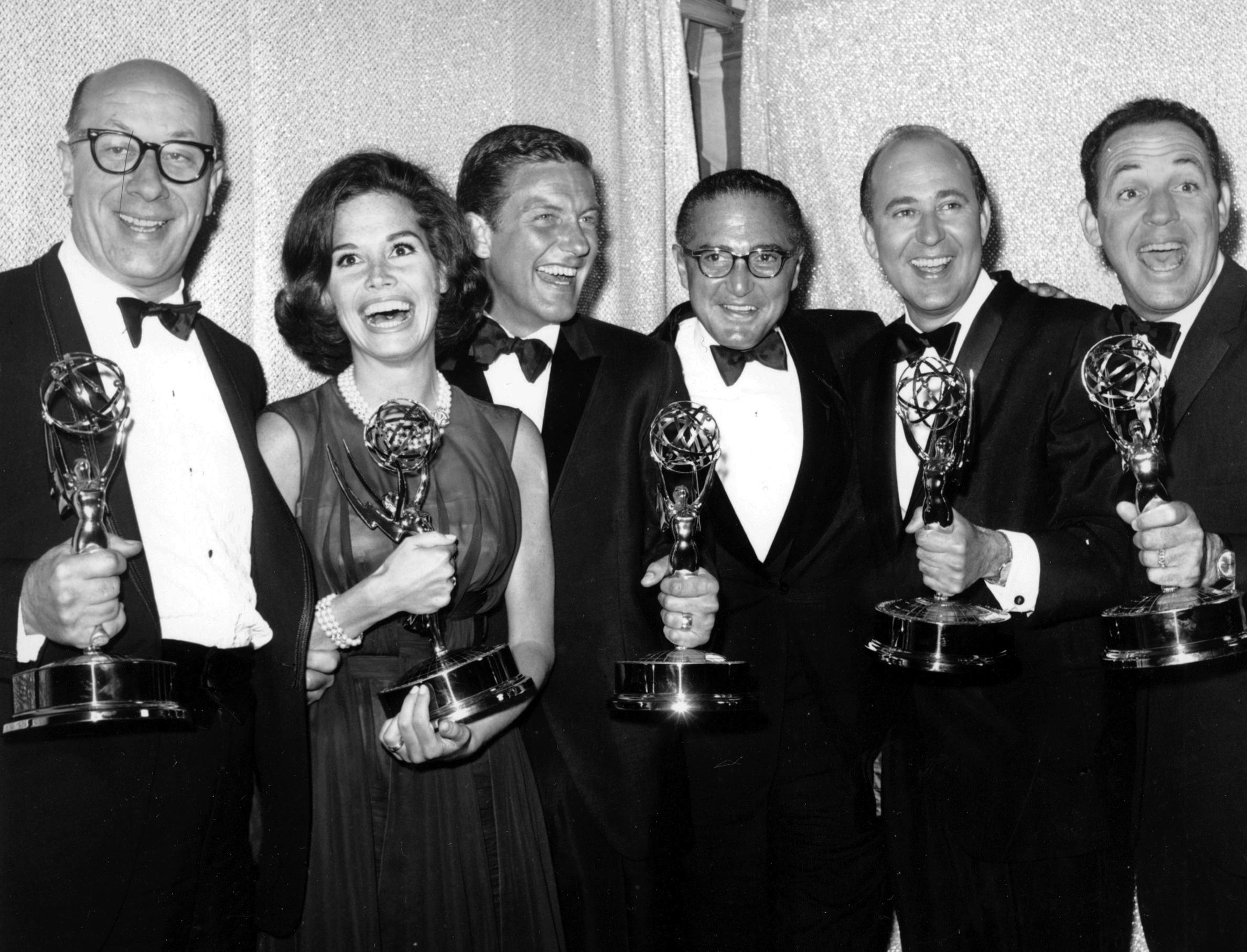 """FILE - In this May 24, 1964 file photo, cast and crew of the television comedy series """"The Dick Van Dyke Show"""" from left, Richard Deacon, Mary Tyler Moore, Outstanding Continued Performance by an Actress in a Series, Lead; Dick Van Dyke, Outstanding Continued Performance by an Actor in a Series, Lead; Sheldon Leonard, producer of the show, which was named best comedy series; Carl Reiner, Outstanding Writing Achievement in a Series; and Jerry Paris, Outstanding Directorial Achievement in Comedy. pose with their awards at the 16th Annual Emmy Awards in Los Angeles. Variety reported that Reiner died of natural causes on Monday night, June 29, 2020, at his home in Beverly Hills, Calif. He was 98. (AP Photo, File)"""