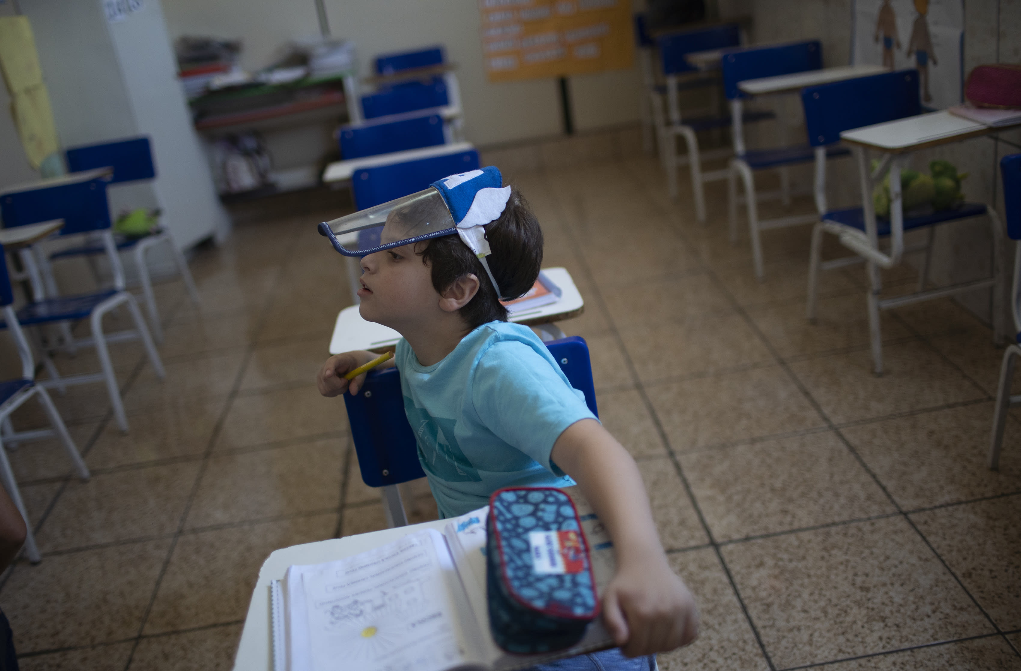Bernardo Santo attends a class wearing a face shield, at the Pereira Agustinho daycare, nursery school and pre-school, after it reopened amid the new coronavirus pandemic in Duque de Caxias, Monday, July 6, 2020. The city of Manaus in the Amazon rainforest and Duque de Caxias in Rio de Janeiro's metropolitan region, became on Monday the first Brazilian cities to resume in-person classes at private schools since the onset of the COVID-19 pandemic, according to the nation's private school federation. (AP Photo/Silvia Izquierdo)