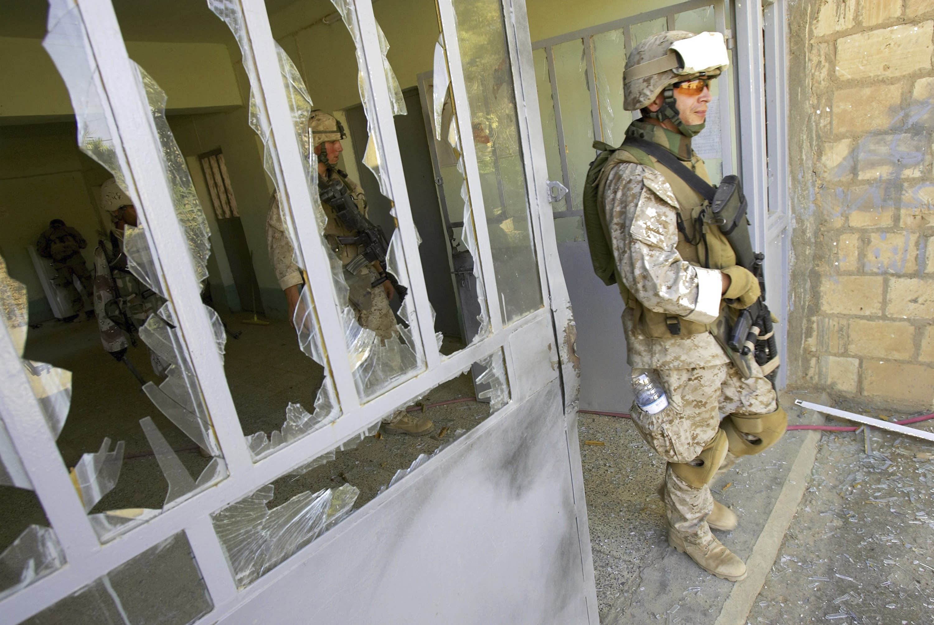 FILE—This file photo from Aug. 6, 2005, shows U.S. Marine Staff Sgt. Brian Hamilton of Columbus, Ohio, from Lima Company of the 3rd Battalion, 25th Regiment as he exits after searching a school, in Parwana, near Haditha, Iraq. Days before, a nearby roadside bomb killed 14 Marines, many from this platoon, and a civilian interpreter on August 3, 2005. Some survivors and families of those killed had planned a 15-year reunion this weekend, but it had to be canceled amid restrictions for the COVID-19 pandemic. (AP Photo/Jacob Silberberg, File)