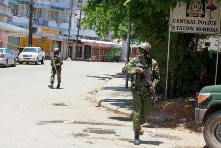 Armed policemen walk outside the central police station after an attack, in the coastal city of Mombasa