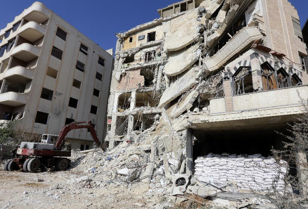 A bulldozer clears debris from the site of a reported Israeli air raid that killed , Samir Kantar of Hezbollah in Damascus on December 20, 2015 (AFP Photo/Louai Beshara)