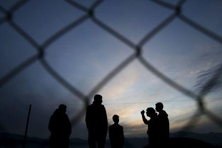 Migrants who are waiting to cross the Greek-Macedonian border, chat at a makeshift camp near the village of Idomeni, Greece March 8, 2016. REUTERS/Marko Djurica