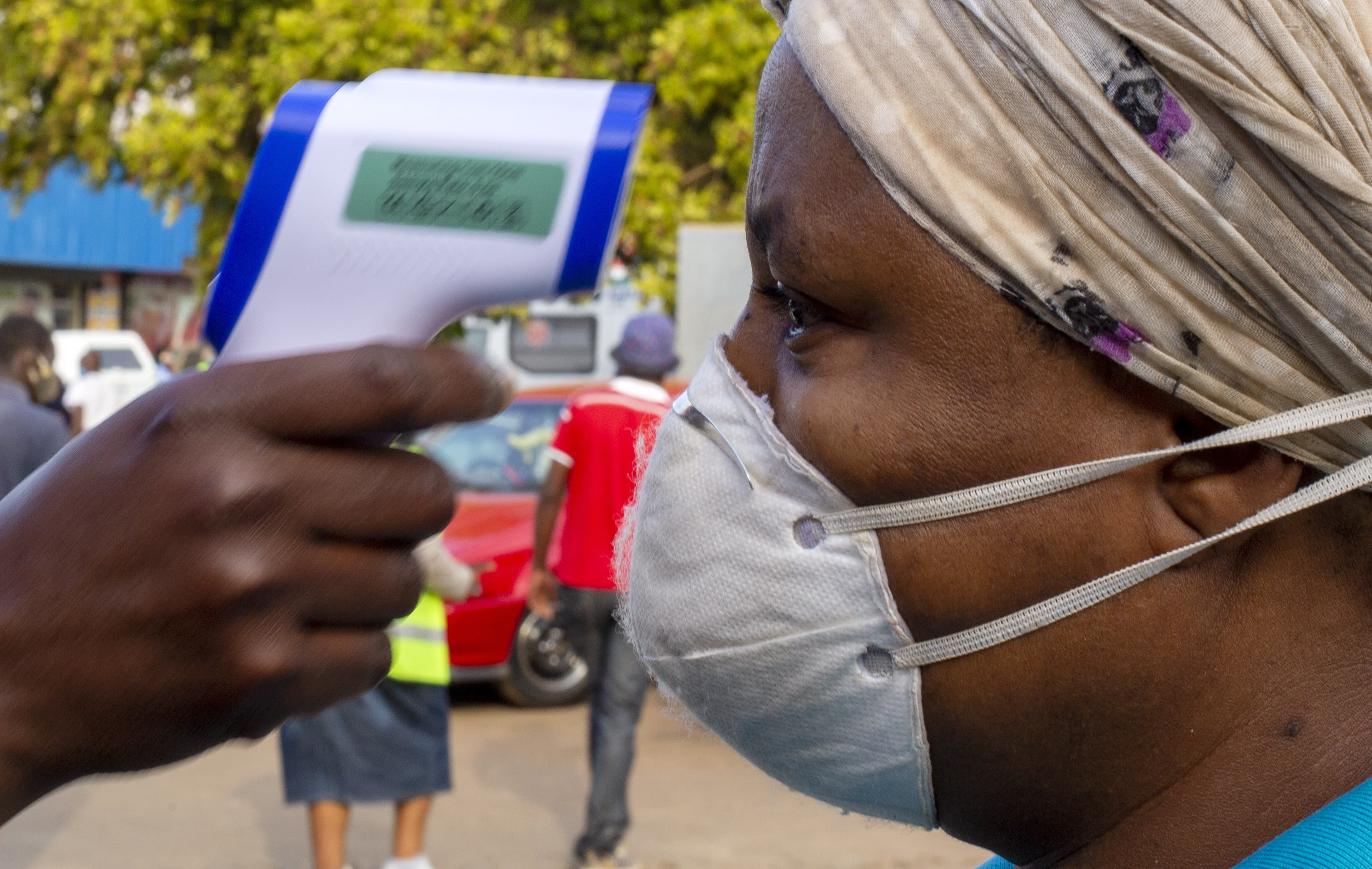 A woman wearing face masks to protect against coronavirus, has her temperature checked by a security personnel before entering a grocery shop at Tembisa township in Johannesburg, South Africa, Tuesday, May 19, 2020. (AP Photo/Themba Hadebe)