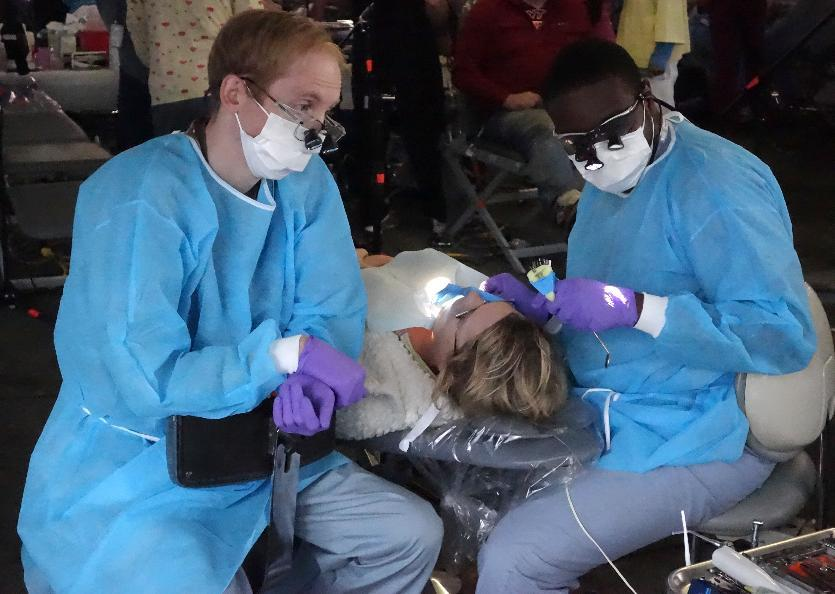 Dentists with Remote Area Medical(RAM), work on patients July 18, 2014 during a mobile clinic event in Wise, Virginia (AFP Photo/Will Edwards)