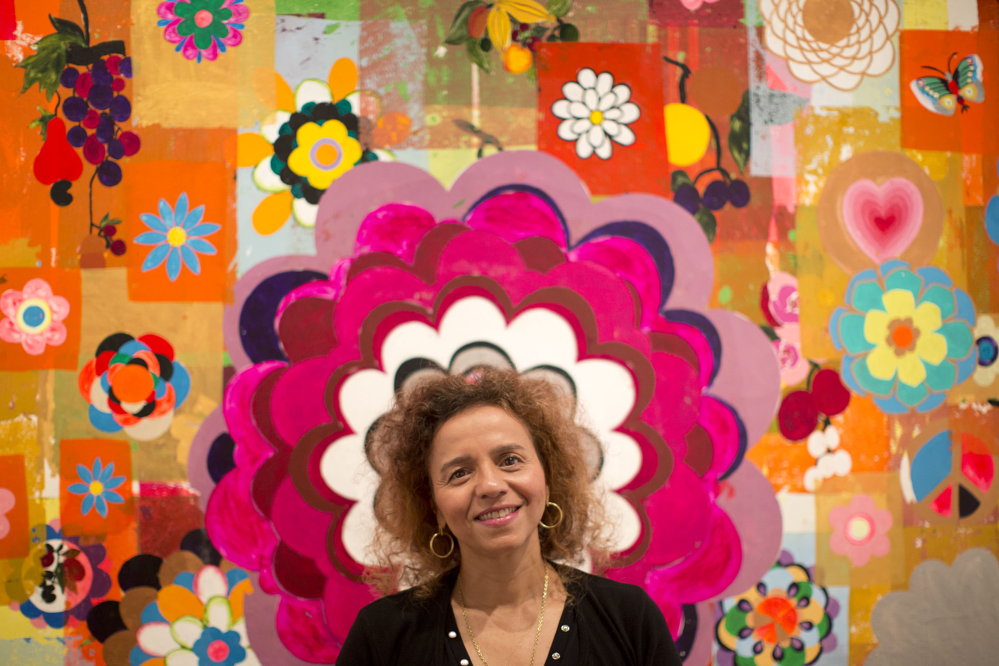 Brazilian artist Beatriz Milhazes poses for a portrait in front of one of her paintings in Rio de Janeiro, Brazil, Friday, Aug. 23, 2013. More than a decade after her last show in her native Rio de Janeiro, Brazil's highest-paid artist is gearing up for a homecoming of sorts, a major retrospective spanning most of her 30-year career. (AP Photo/Felipe Dana)