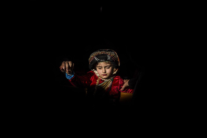 <p>A Christian Iraqi girl holds her mothers hand during the celebration of Santa Barbara in Om Al-Auna church in Irbil, Iraq, Dec. 9, 2016. (Photo: Manu Brabo/AP) </p>