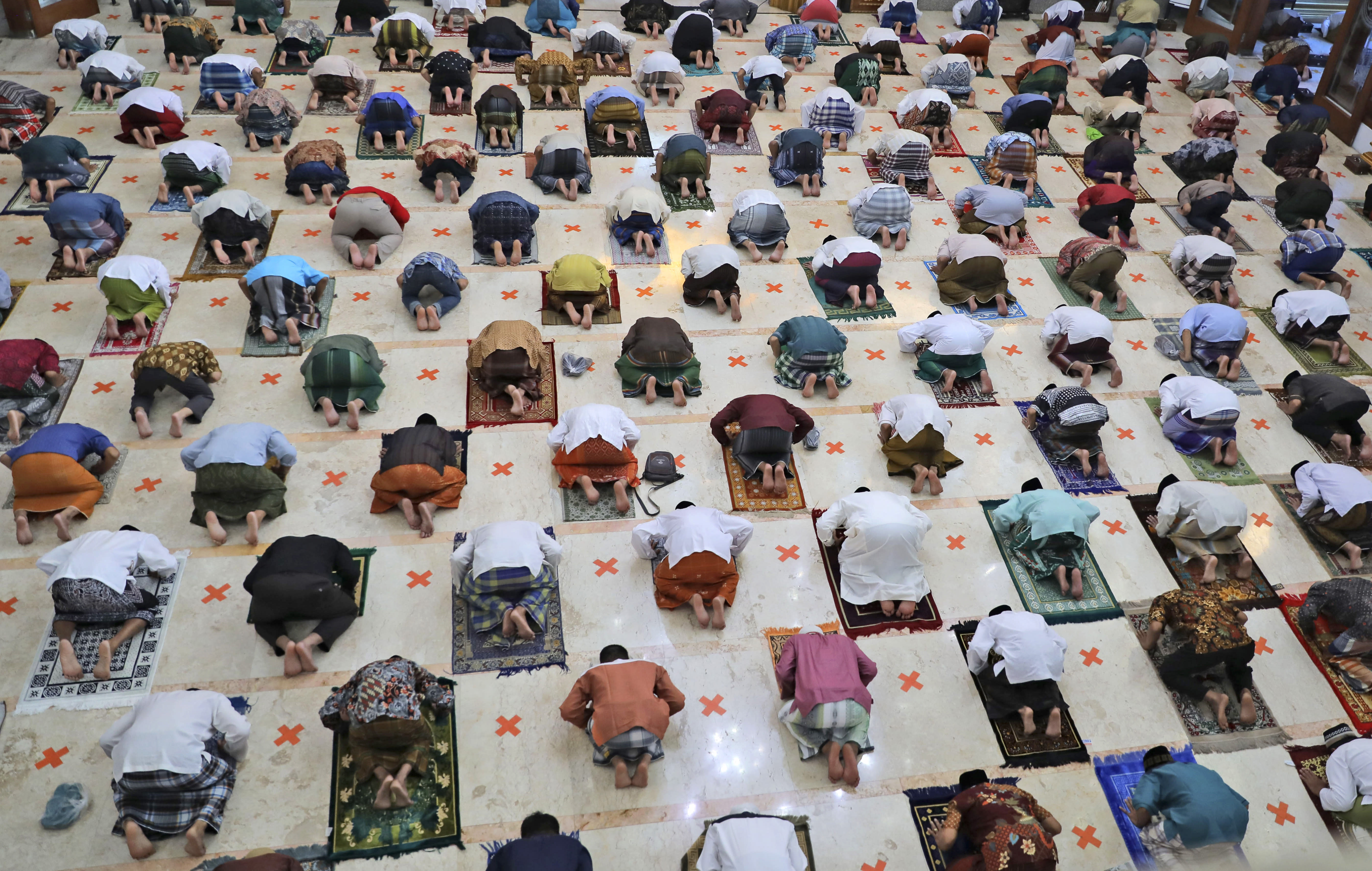 Indonesian Muslims pray spaced apart as they practice social distancing to curb the spread of the new coronavirus during an Eid al-Fitr prayer marking the end of the holy fasting month of Ramadan in Sidoarjo, East Java, Indonesia, Sunday, May 24, 2020. Millions of people in the world's largest Muslim nation are marking a muted and gloomy religious festival of Eid al-Fitr, the end of the fasting month of Ramadan _ a usually joyous three-day celebration that has been significantly toned down as coronavirus cases soar. (AP Photo/Trisnadi)