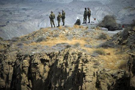 Members of Iran's Revolutionary guard personnel monitor an area as they stand on top of a hill while taking part in a war game in the Hormuz area of southern Iran