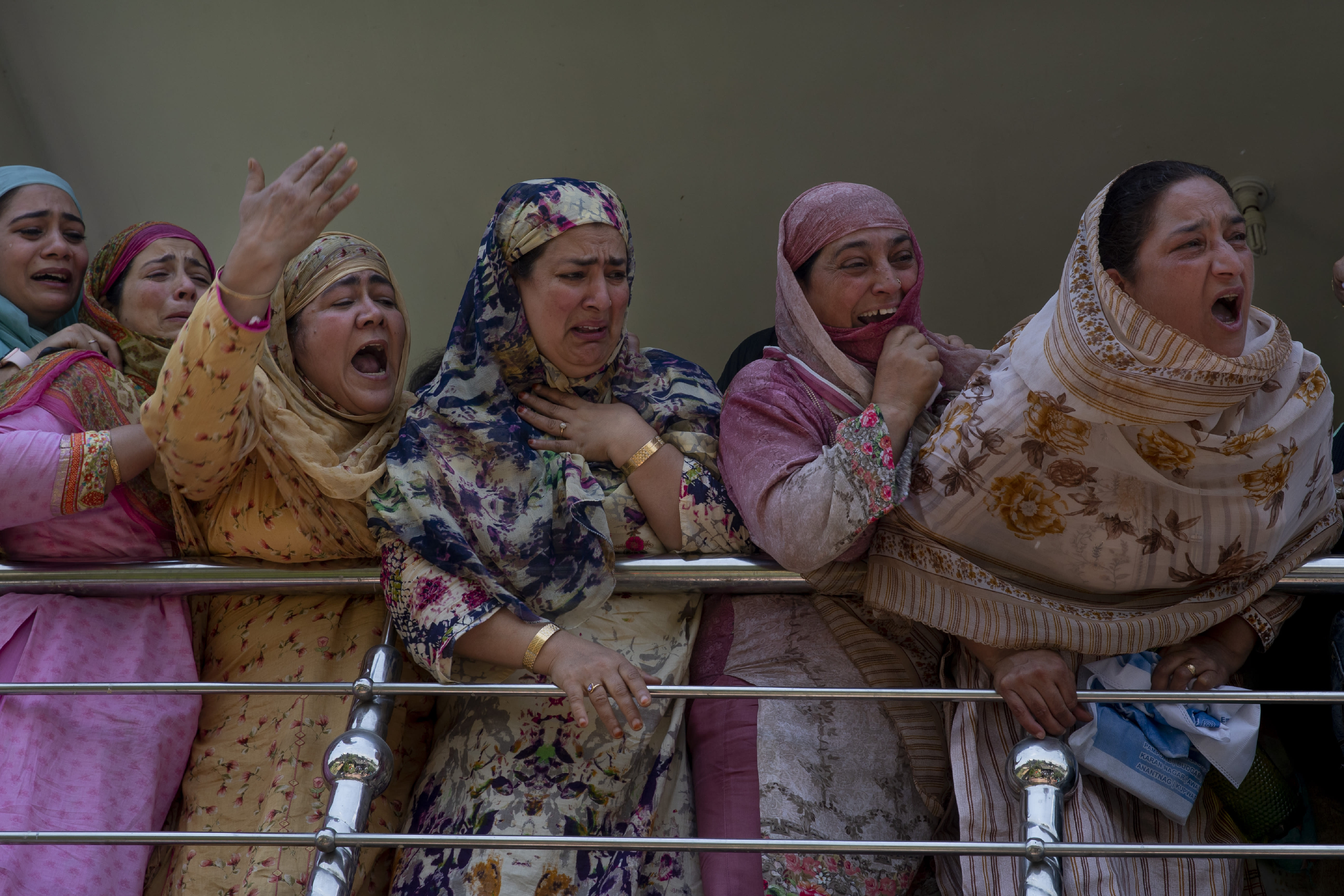 Relatives of Kashmiri civilian Bashir Ahmed Khan grieve as they watch his funeral on the outskirts of Srinagar, Indian controlled Kashmir, Wednesday, July 1, 2020. Suspected rebels attacked paramilitary soldiers in the Indian portion of Kashmir, killing Khan and a paramilitary soldier, according to government sources. The family refutes the claim. (AP Photo/ Dar Yasin)