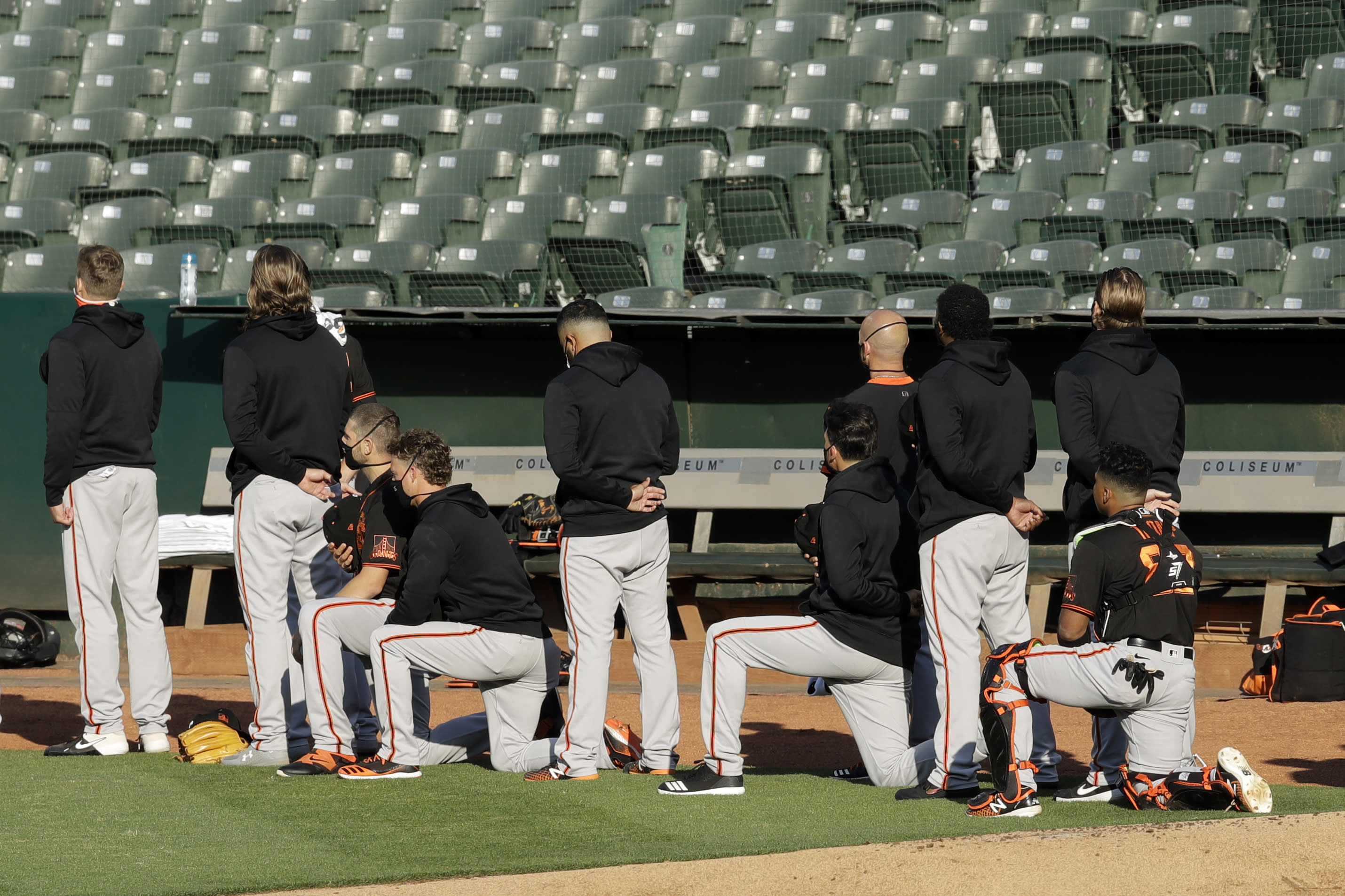 Some San Francisco Giants kneel during the national anthem prior to an exhibition baseball game against the Oakland Athletics on Monday, July 20, 2020, in Oakland, Calif. (AP Photo/Ben Margot)