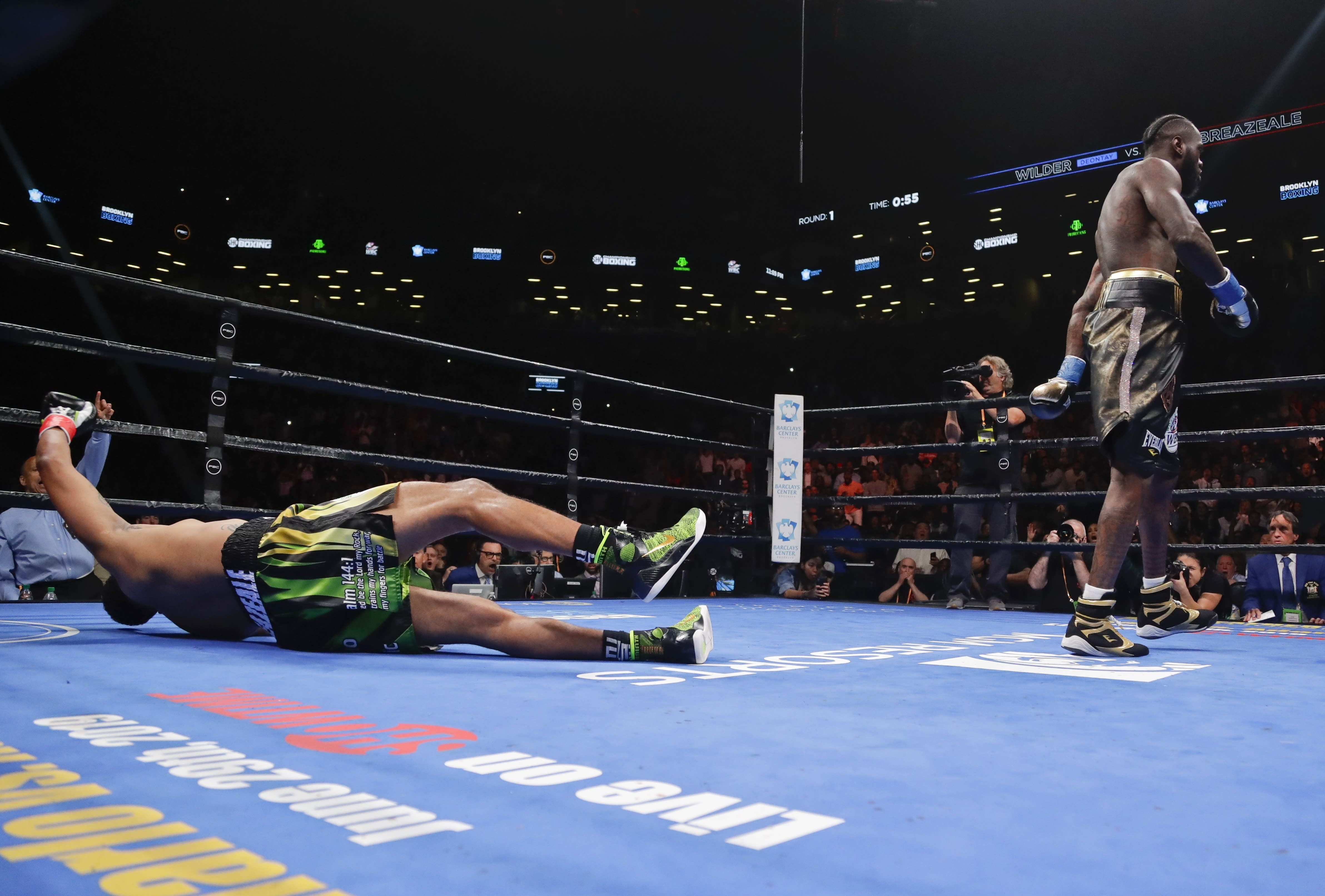 Deontay Wilder, right, knocks down Dominic Breazeale during the first round of the WBC heavyweight championship boxing match Saturday, May 18, 2019, in New York. Wilder won in the first round. (AP Photo/Frank Franklin II)