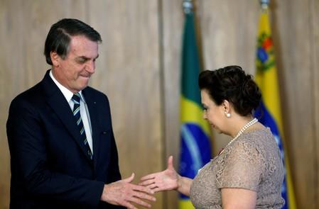 Brazil's President Jair Bolsonaro shakes hands with Venezuela's ambassador to Brazil Maria Teresa Belandria during the credentials presentation ceremony of several new diplomats, in Brasilia