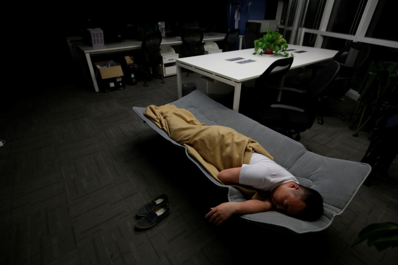 Ma Zhenguo, a systems engineer at RenRen Credit Management Co., sleeps on a camp bed at the office after finishing work early in the morning in Beijing on April 27, 2016. (Jason Lee/Reuters)
