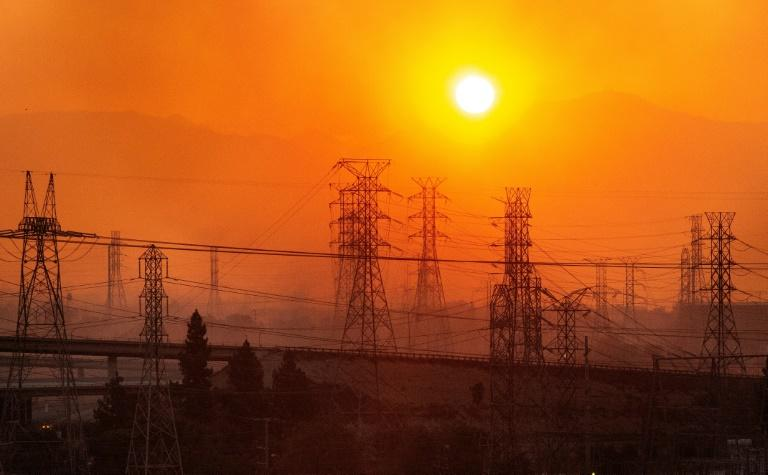The sun rises over power lines along a smokey horizon during the Saddleridge Fire in Newhall, California on October 11, 2019 (AFP Photo/Josh Edelson)
