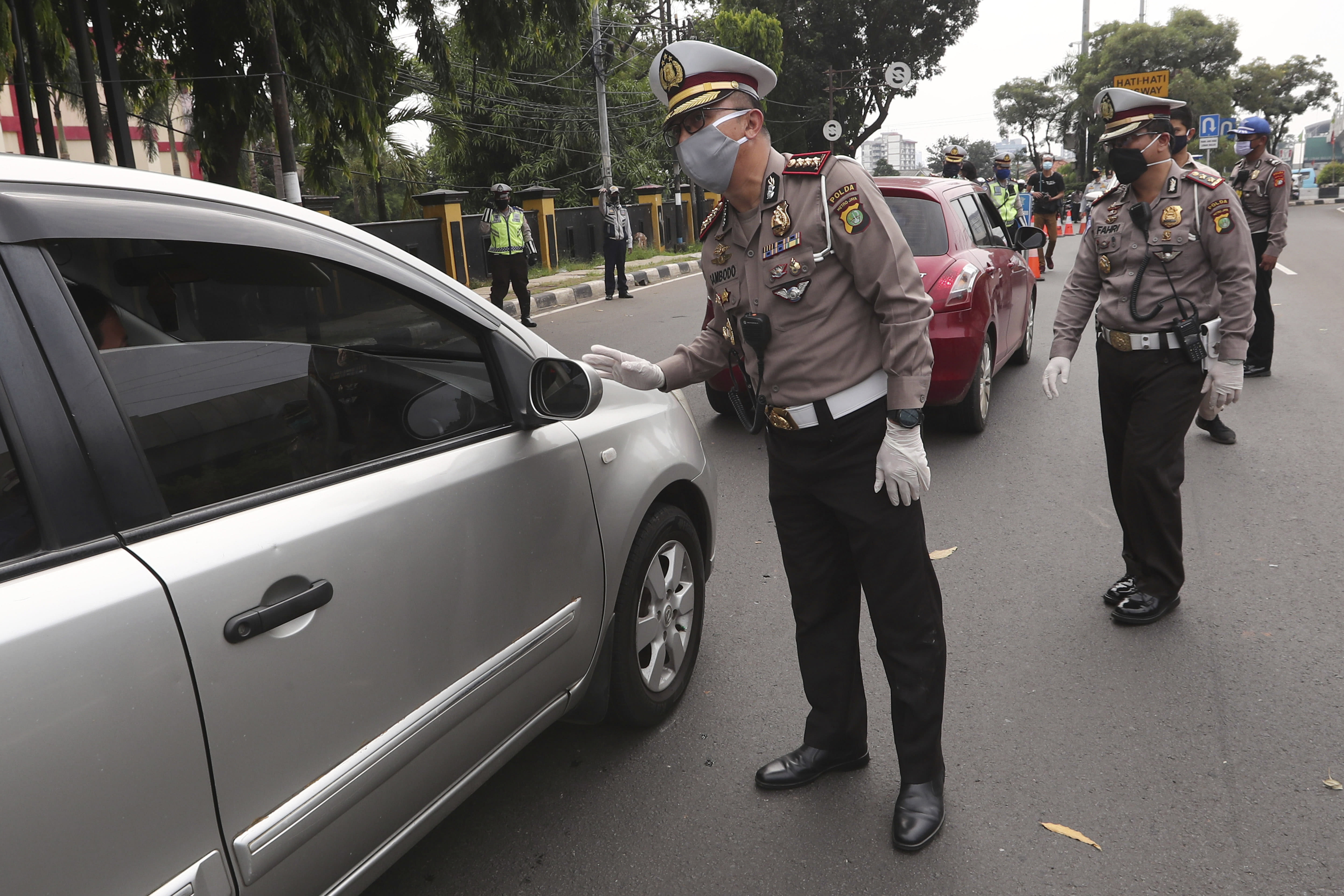 Police officers check the number of people seated inside a car during the imposition of large-scale social restriction, at a checkpoint in Jakarta, Indonesia, Friday, April 10, 2020. Authorities in Indonesia's capital kicked off a stricter restriction on Friday to slow the spread of the new coronavirus in the city where deaths from the virus has spiked in the past week. (AP Photo/Tatan Syuflana)