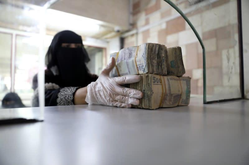 Employee takes bundles of Yemeni Riyal at the Central Bank of Yemen in Sanaa