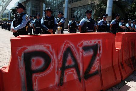 "Police stand behind a barricade, with the writing ""Peace"" on it, to block protesters as a meeting of the Financial Oversight and Management Board for Puerto Rico is taking place at the Convention Center in San Juan, Puerto Rico March 31, 2017. Picture taken March 31, 2017. REUTERS/Alvin Baez"