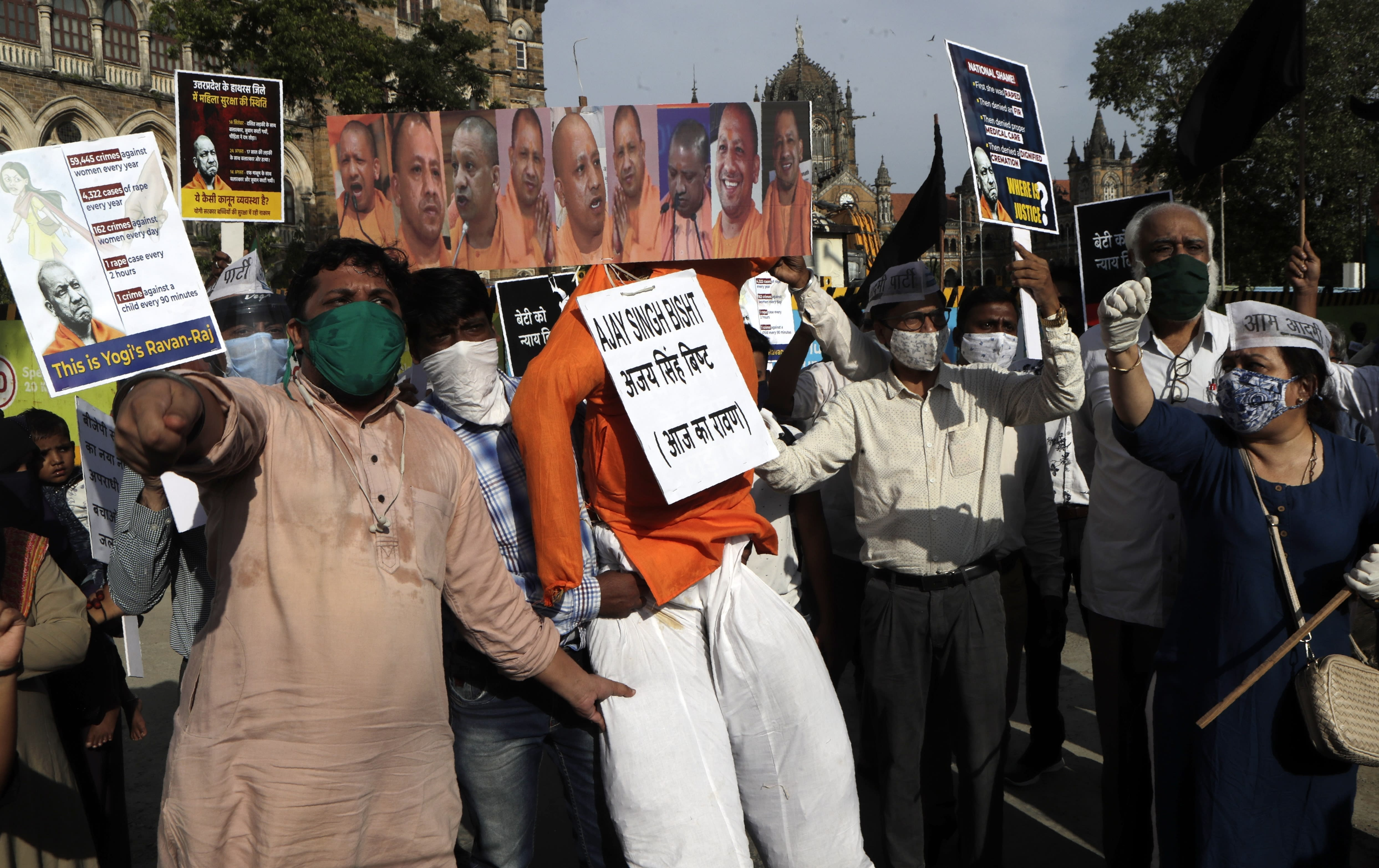Activists protesting against gang rape and killing of a woman in Uttar Pradesh's Hathras district shout slogans and beat an effigy of Uttar Pradesh state Chief Minister Yogi Adityanath in Mumbai, India, Thursday, Oct. 1, 2020. The gang rape and killing of the woman from the lowest rung of India's caste system has sparked outrage across the country with several politicians and activists demanding justice and protesters rallying on the streets. (AP Photo/Rajanish Kakade)