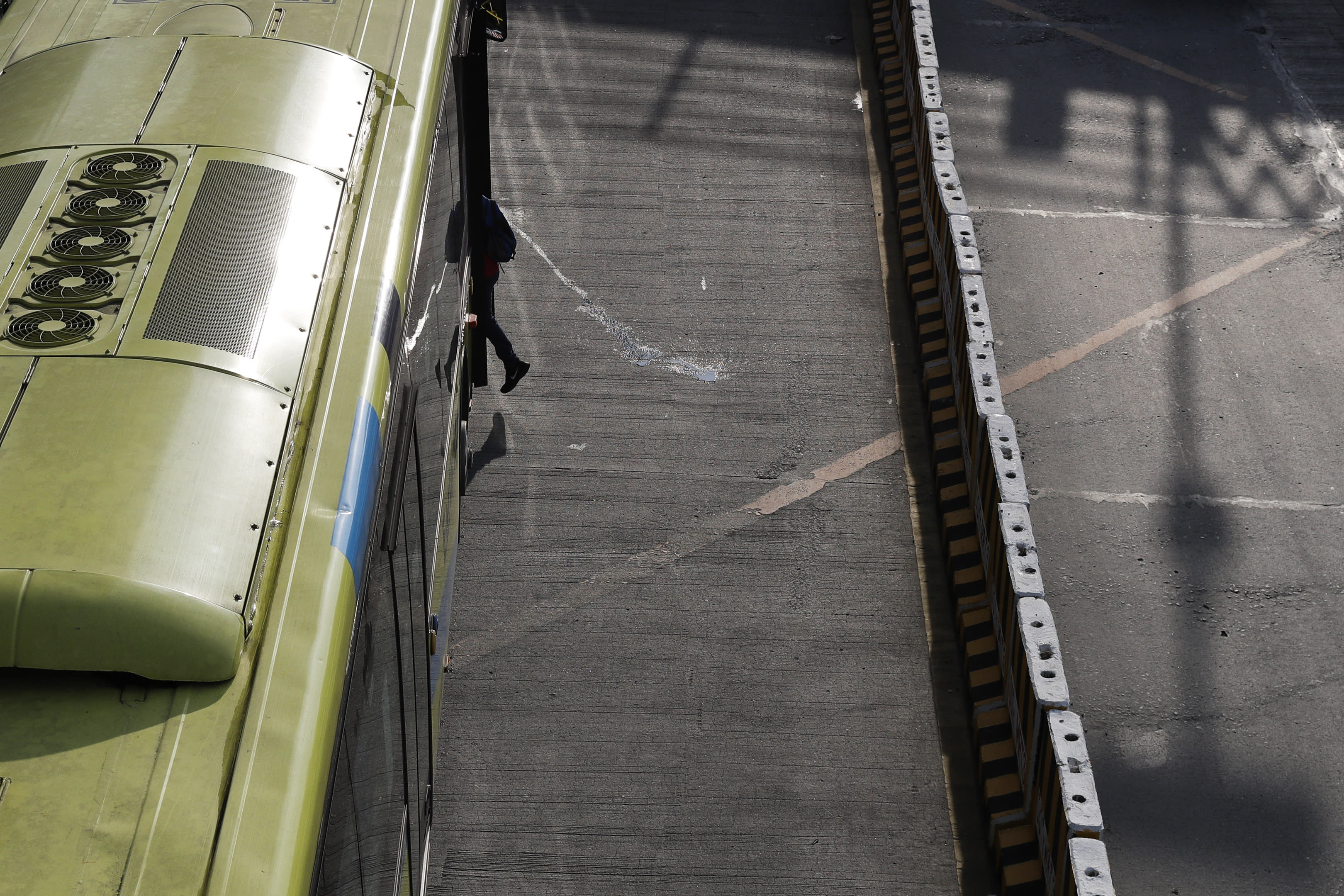 A man boards a bus in Quezon city, Philippines, Saturday, Sept. 26, 2020. Public transportation remains limited and the government orders commuters to wear face shields and face masks to help curb the spread of the coronavirus. (AP Photo/Aaron Favila)