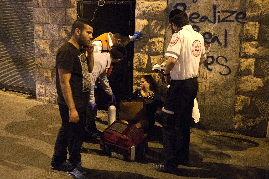 A woman is treated by medics at the site where a knife-wielding man stabbed and wounded a woman near Jerusalem's central bus station on October 14, 2015 (AFP Photo/Menahem Kahana)