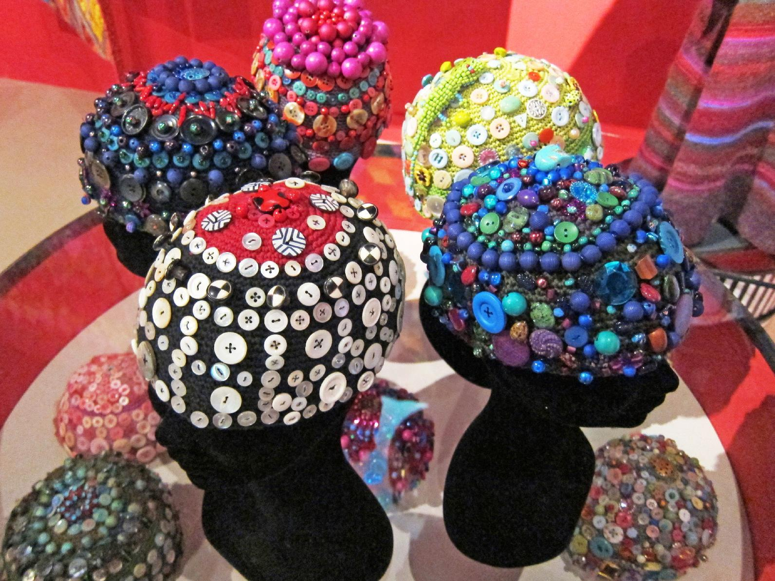 """This publicity photo provided by Kaffe Fassett Studio shows textile artist Kaffe Fassett's crocheted skull caps, which are embellished with buttons and beads. Dozens of similar caps appeared in the show """"Kaffe Fassett: A Life in Colour"""" recently at the Fashion and Textile Museum in London. Today's crochet is leaner and trendier than that of the 1960s and '70s, from which we know it for its bulky, acrylic yarns and Afghan blankets. (AP Photo/Kaffe Fassett Studio)"""