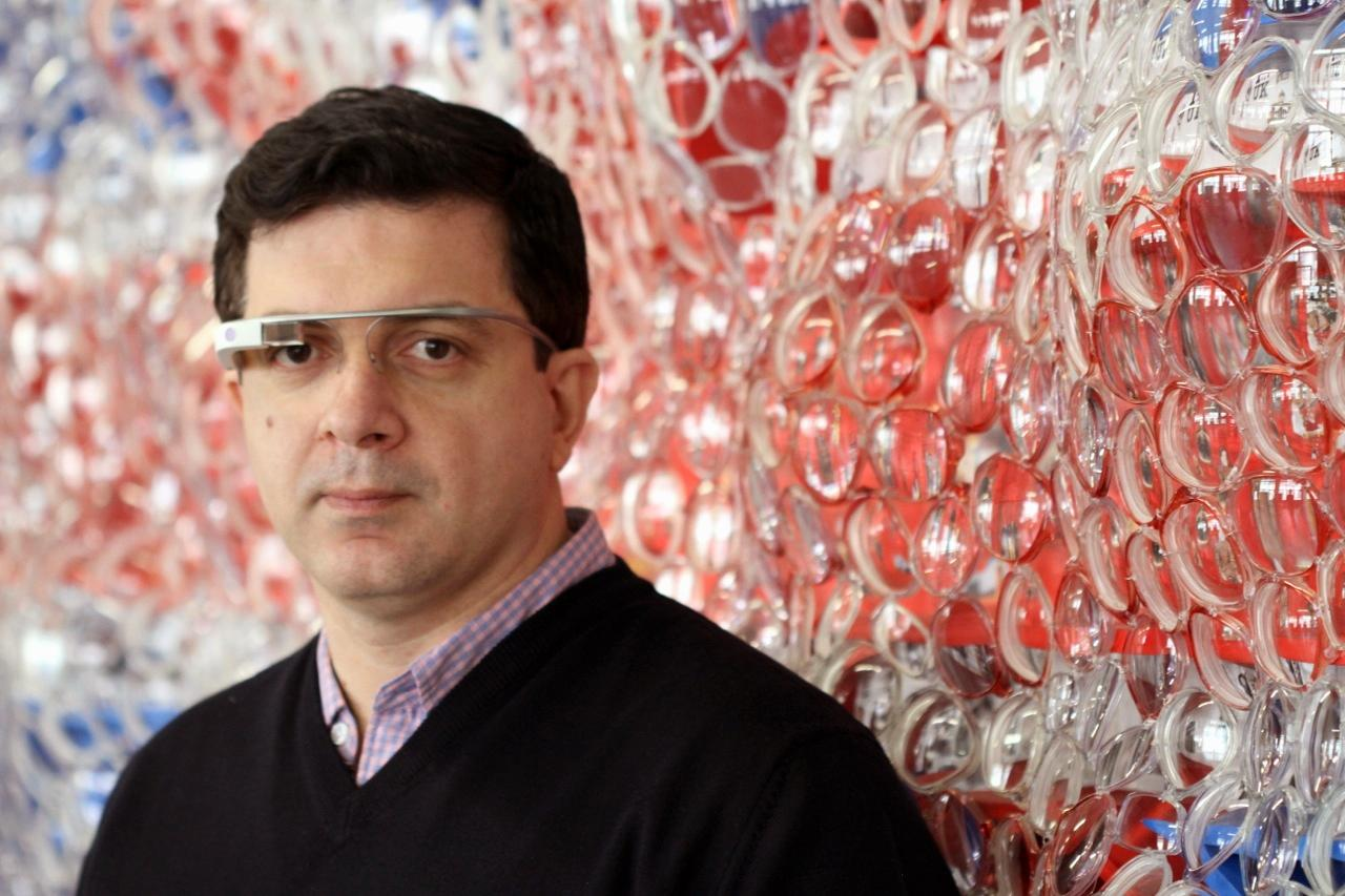 "This undated image provided by Kiwi Arts Group shows David Datuna wearing a Google Glass device, with one of the works from his ""Viewpoint of Billions"" series behind him. Google Glass devices will be available during Art Basel Miami Beach, Dec. 5-8, for use by the public in interacting with Datuna's works. (AP Photo/Kiwi Arts Group)"