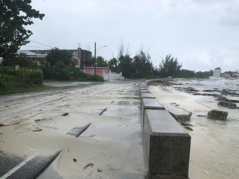 Sand pours onto a road near the beach in Nassau, Bahamas during the approach of Hurricane Dorian (AFP Photo/Lucy WORBOYS)