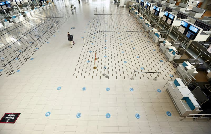 FILE PHOTO: A passenger walks past empty check-in counters at Cape Town International Airport