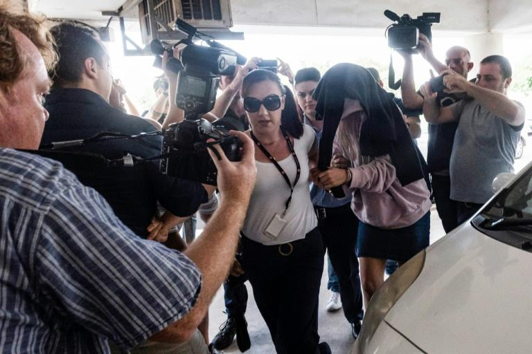 A British teenager who accused seven Israelis of gang rape arrives at court with her head covered to shield her from a media barrage on the holiday island of Cyprus