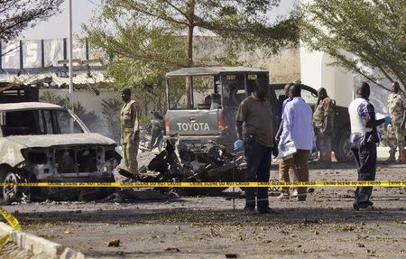 Bomb detection experts and members of the military stand at the scene of an explosion at a police station in Kano November 15, 2014. REUTERS/Stringer