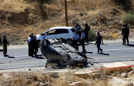 Israeli security forces gather at the scene following a shooting on an Israeli car near the West Bank city of Hebron July 1, 2016. REUTERS/Mussa Qawasma/File Photo