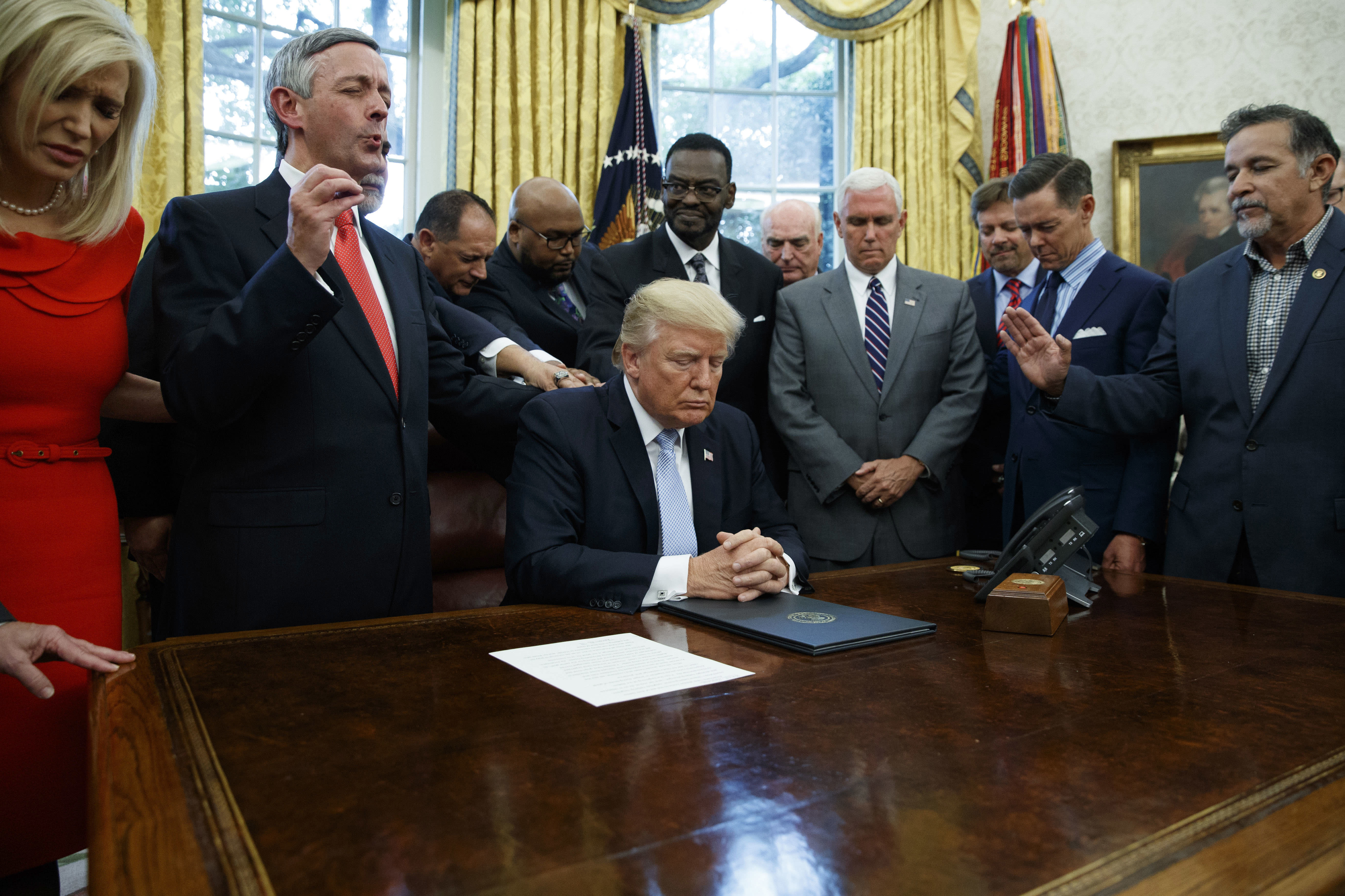 FILE - In this Sept. 1, 2017 file photo, religious leaders pray with President Donald Trump after he signed a proclamation for a national day of prayer to occur on Sunday, Sept. 3, 2017, in the Oval Office of the White House in Washington. Religion's role in politics and social policies is in the spotlight heading toward the midterm elections, yet relatively few Americans consider it crucial that a candidate be devoutly religious or share their religious beliefs, according to an AP-NORC national poll conducted Aug. 16-20, 2018. (AP Photo/Evan Vucci)