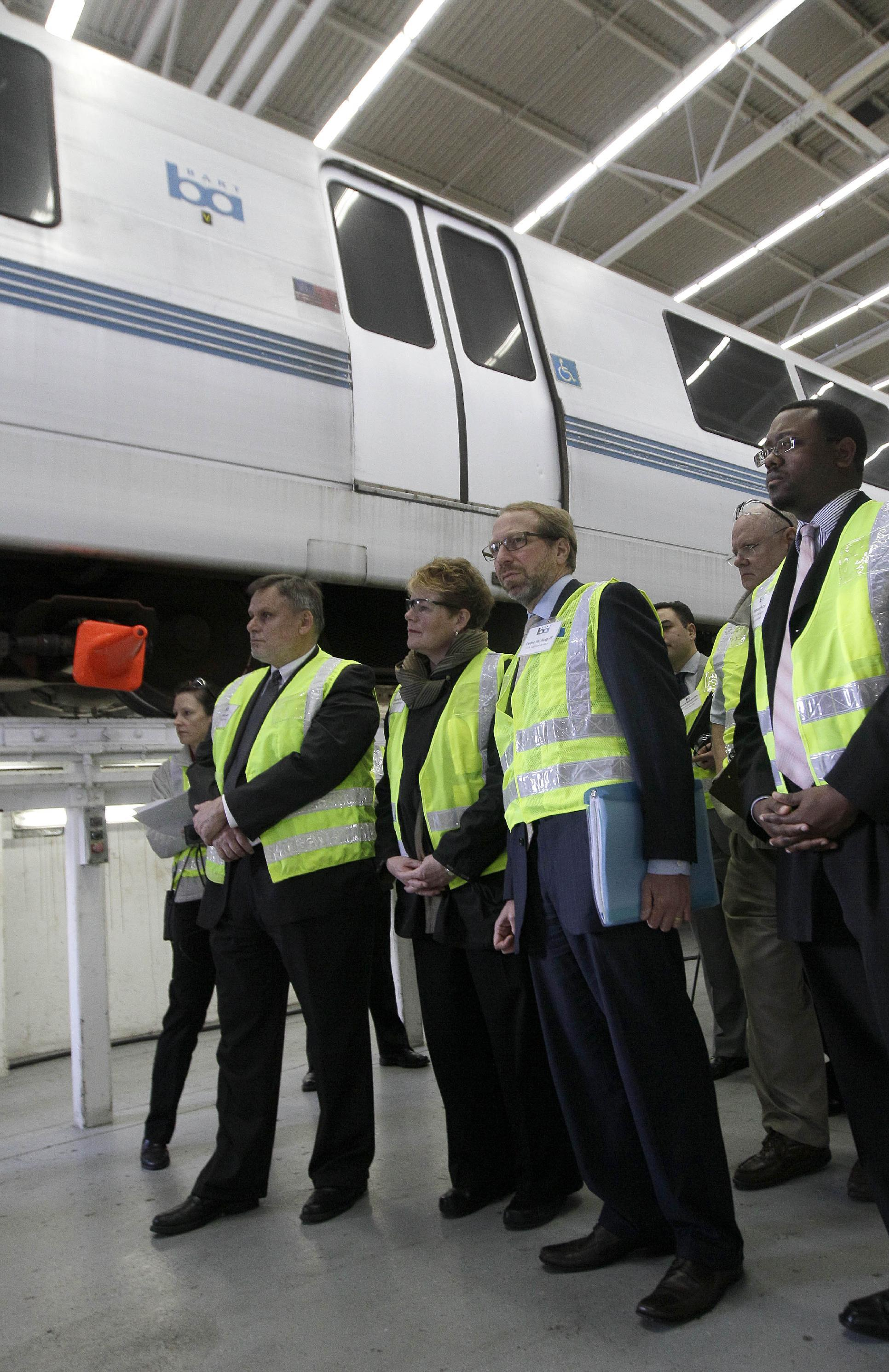 In this photo taken Wednesday, April 11, 2012, Federal Transit Administrator Peter Rogoff, second from right, and Bay Area Rapid Transit (BART) General Manager Grace Crunican, second from left, and others, stand near a BART train during a tour of the BART Maintenance Yard in Hayward, Calif. Driven by high gas prices and an uncertain economy, Americans are turning to trains and buses to get around in greater numbers than ever before. The aging trains and buses they're riding, however, face an $80 billion maintenance backlog that jeopardizes service just when it's most in demand. (AP Photo/Jeff Chiu)