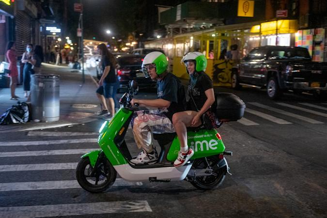 NEW YORK, NEW YORK - MAY 22: People without masks drive around on a Lime E-moped in the Lower East Side on May 22, 2021 in New York City. This is the first Saturday night that New York City is not under pandemic restrictions in more than a year. On May 19, all pandemic restrictions, including mask mandates, social distancing guidelines, venue capacities and restaurant curfews were lifted by New York Governor Andrew Cuomo. (Photo by Alexi Rosenfeld/Getty Images)