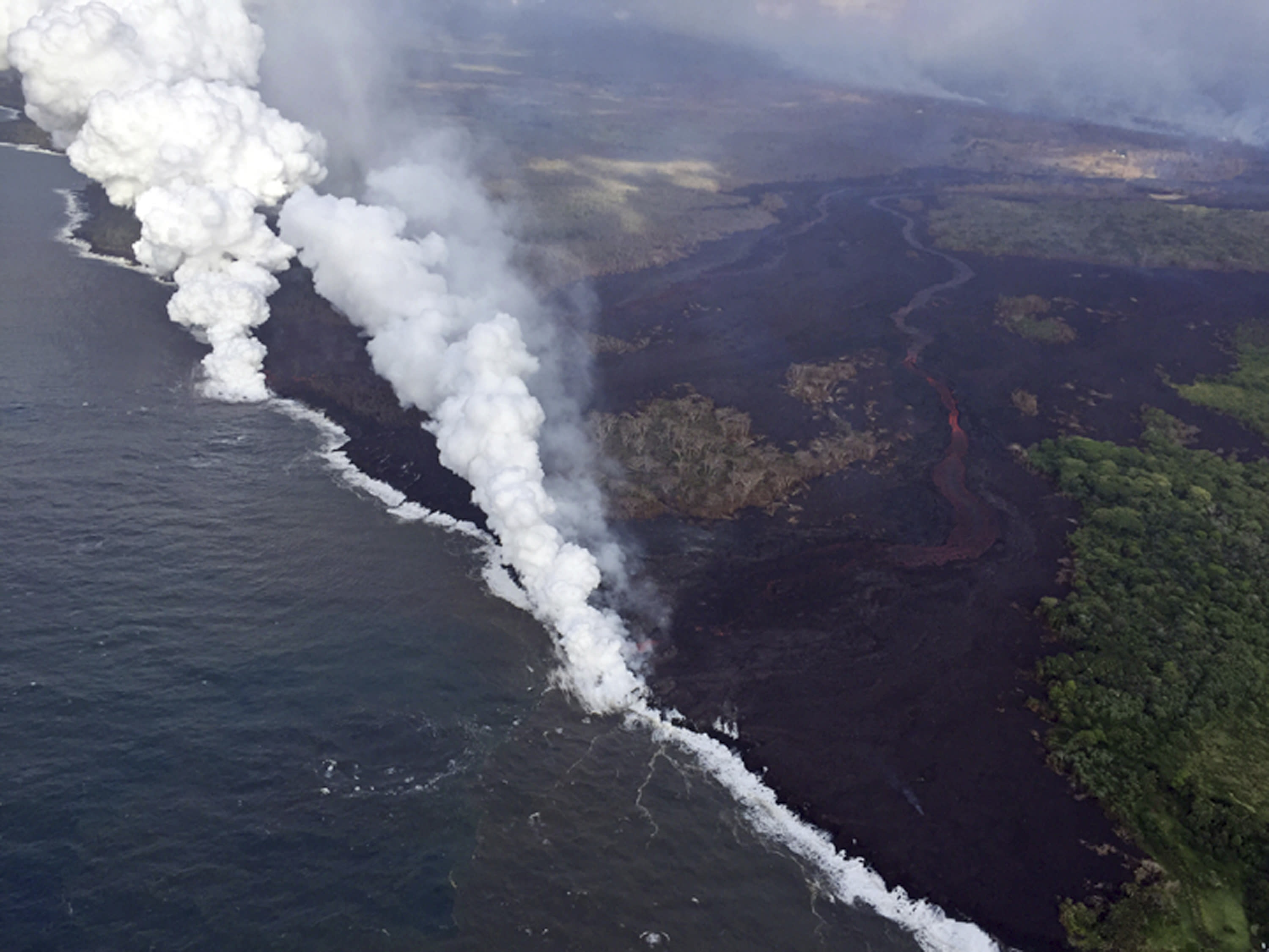 <p>Lava sends up clouds of steam and toxic gases as it enters the Pacific Ocean as Kilauea Volcano continues its eruption cycle near Pahoa on the island of Hawaii Friday, May 25, 2018. (Photo: U.S. Geological Survey via AP) </p>
