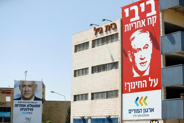 A banner for Israel's Blue and White (Kahol Lavan) electoral alliance bearing the portrait of retired General Benny Gantz hangs on a building, while a billboard shows Prime Minister and Likud party chairman Benjamin Netanyahu (AFP Photo/AHMAD GHARABLI)
