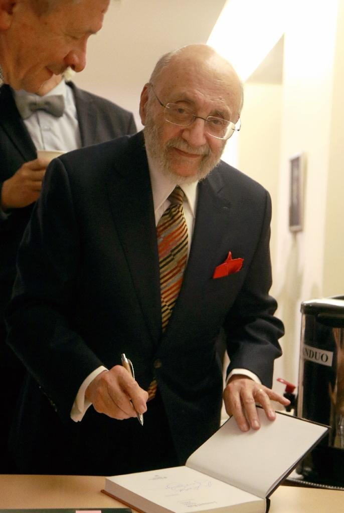 Holocaust survivor Samuel Bak signs a book during the opening of a museum of his allegorical work inspired by Jewish history in the Lithuanian capital Vilnius (AFP Photo/Petras Malukas)