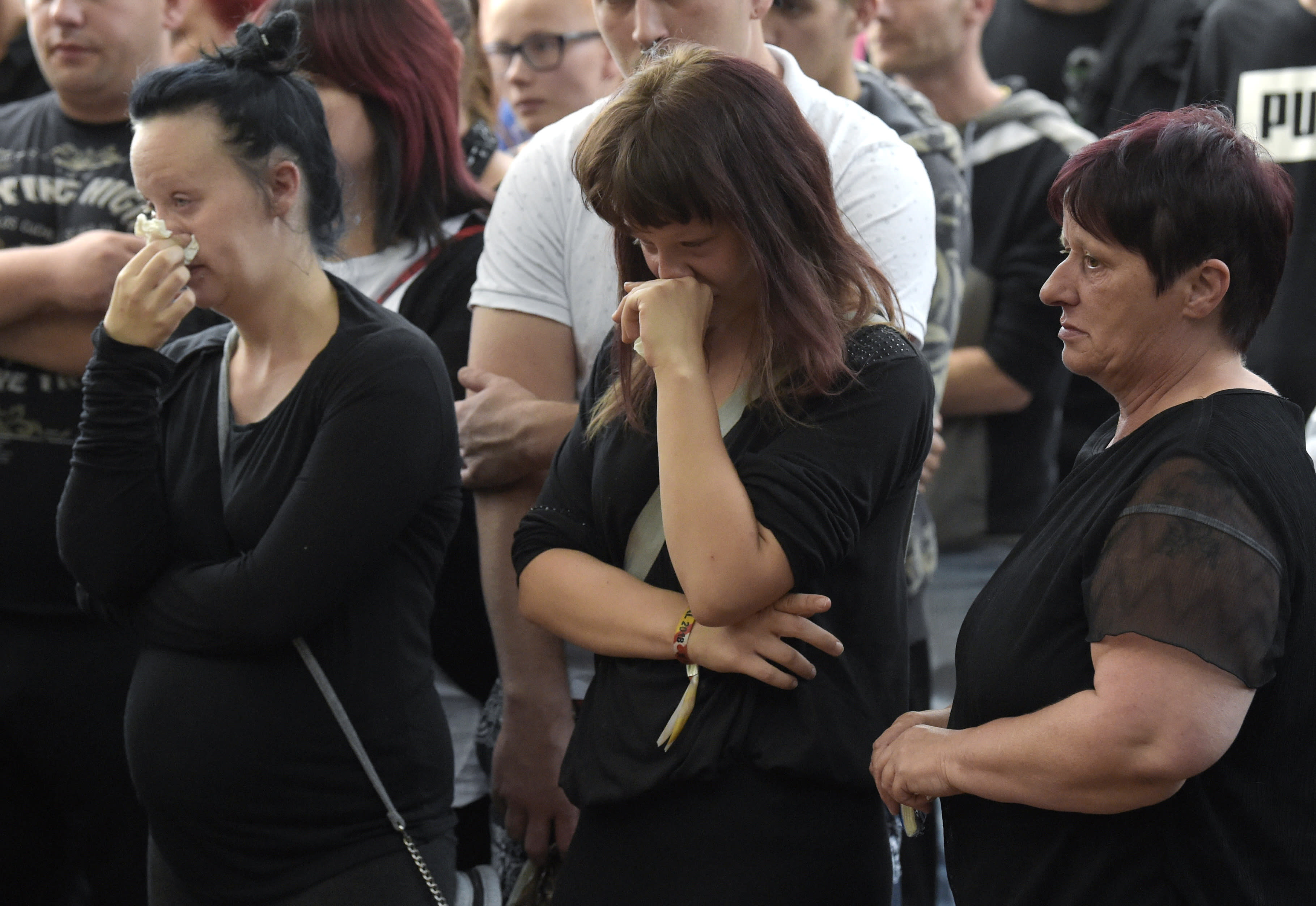Women cry as people gather at the site of a deadly brawl in Koethen, 90 miles southwest of the German capital Berlin, Sunday, Sept. 9, 2018, after police has arrested two Afghan men on suspicion of killing a 22-year-old German man. (AP Photo/Jens Meyer)