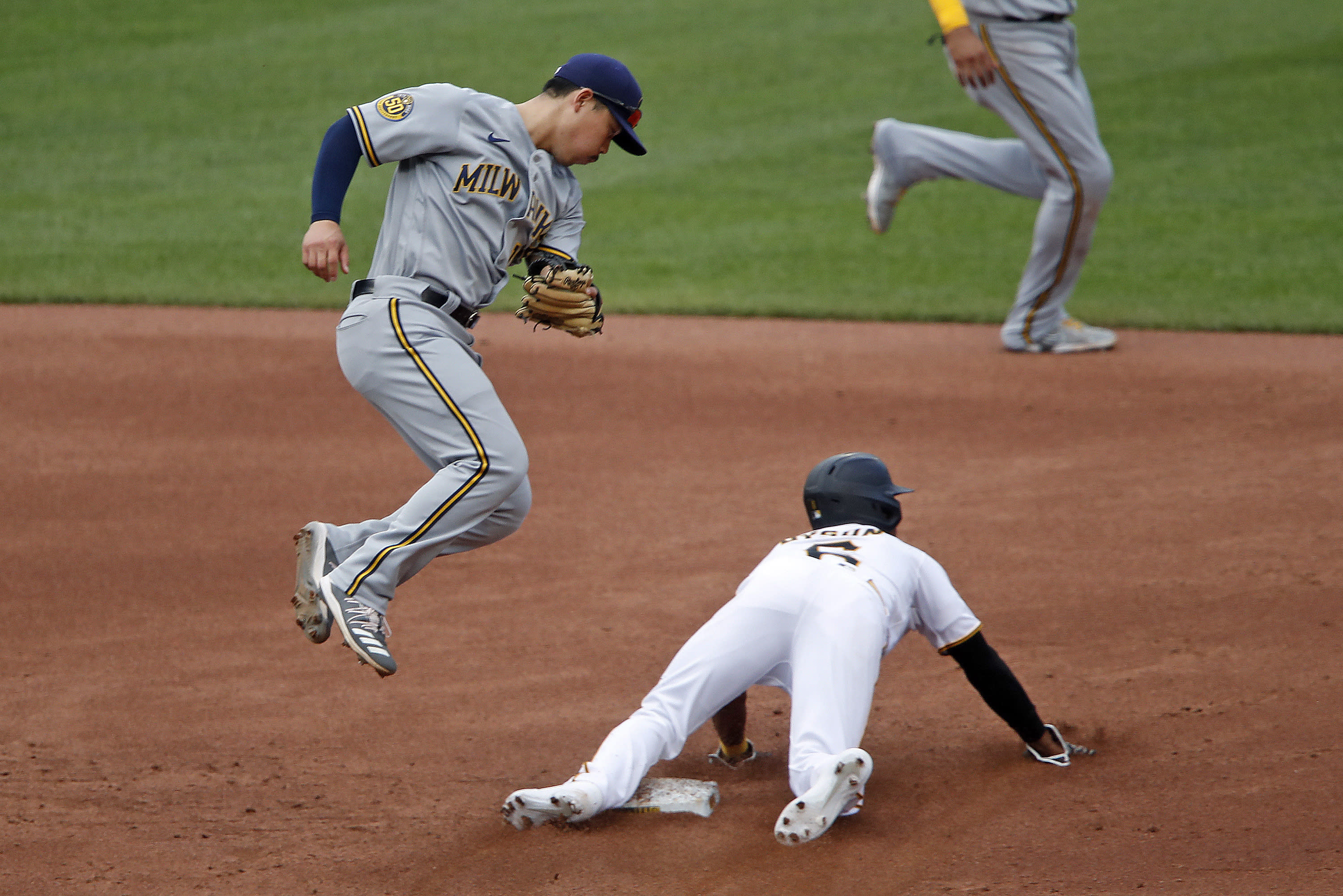 Pittsburgh Pirates' Jarrod Dyson (6) successfully steals second as the high throw from Milwaukee Brewers catcher Omar Narvaez gets past second baseman Keston Hiura, left, during the second inning of a baseball game in Pittsburgh, Sunday, Aug. 23, 2020. Dyson advanced to third on the throwing error. (AP Photo/Gene J. Puskar)