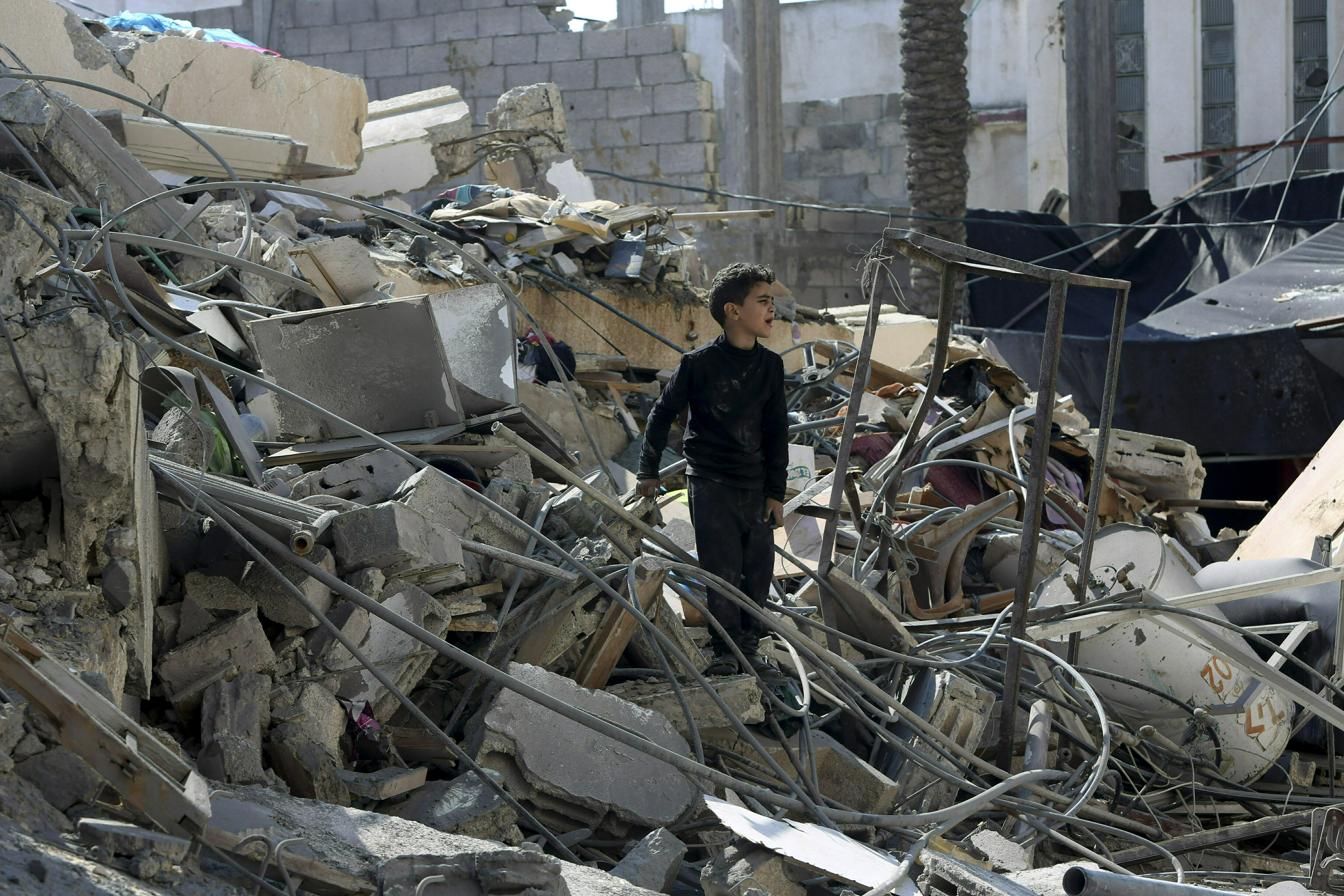 FILE - In this Wednesday, March 27, 2019 file photo, a Palestinian boy searches for their family's belongings amid the rubble of a destroyed building near a Hamas security building that was destroyed in an Israeli airstrike in Gaza City. Hamas controls Gaza more tightly than ever, despite unprecedented domestic unrest and its failure to significantly weaken Israel's chokehold of the territory after a year of weekly anti-blockade rallies along their shared frontier. (AP Photo/Adel Hana, File)