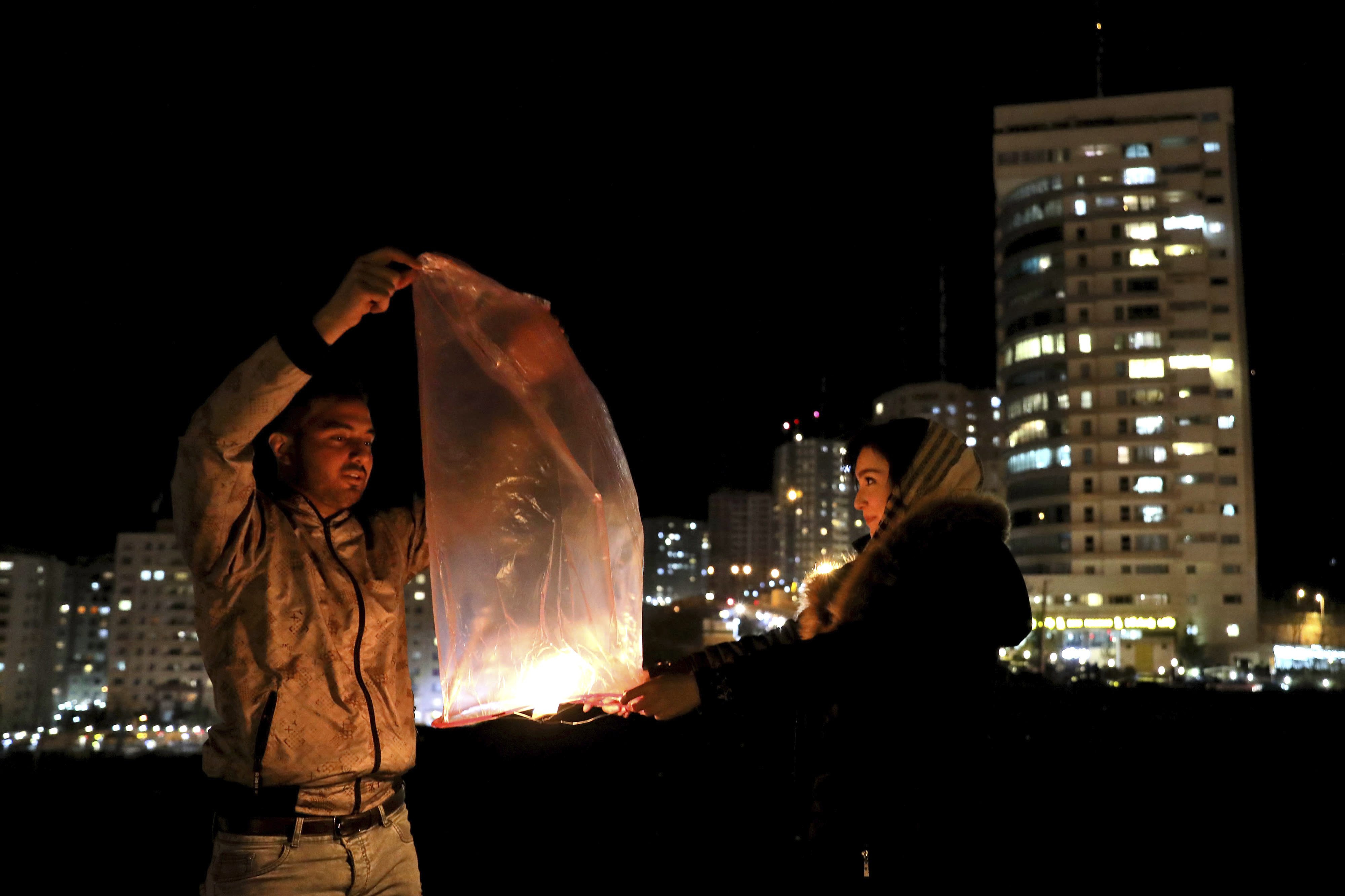 """In this Tuesday, March 17, 2020 photo, two Iranians release a lit lantern during a celebration, known as """"Chaharshanbe Souri,"""" or Wednesday Feast, marking the eve of the last Wednesday of the solar Persian year, in Tehran, Iran. (AP Photo/Ebrahim Noroozi)"""
