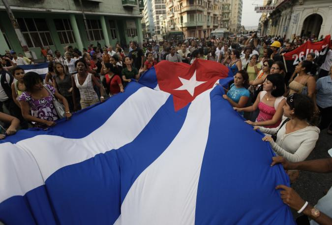 Pro-government youth carry a Cuban flag in front of the Ladies in White, a group made up of family members of imprisoned dissidents, during a protest march in Havana March 25, 2010.  REUTERS/Desmond Boylan (CUBA - Tags: POLITICS CIVIL UNREST)