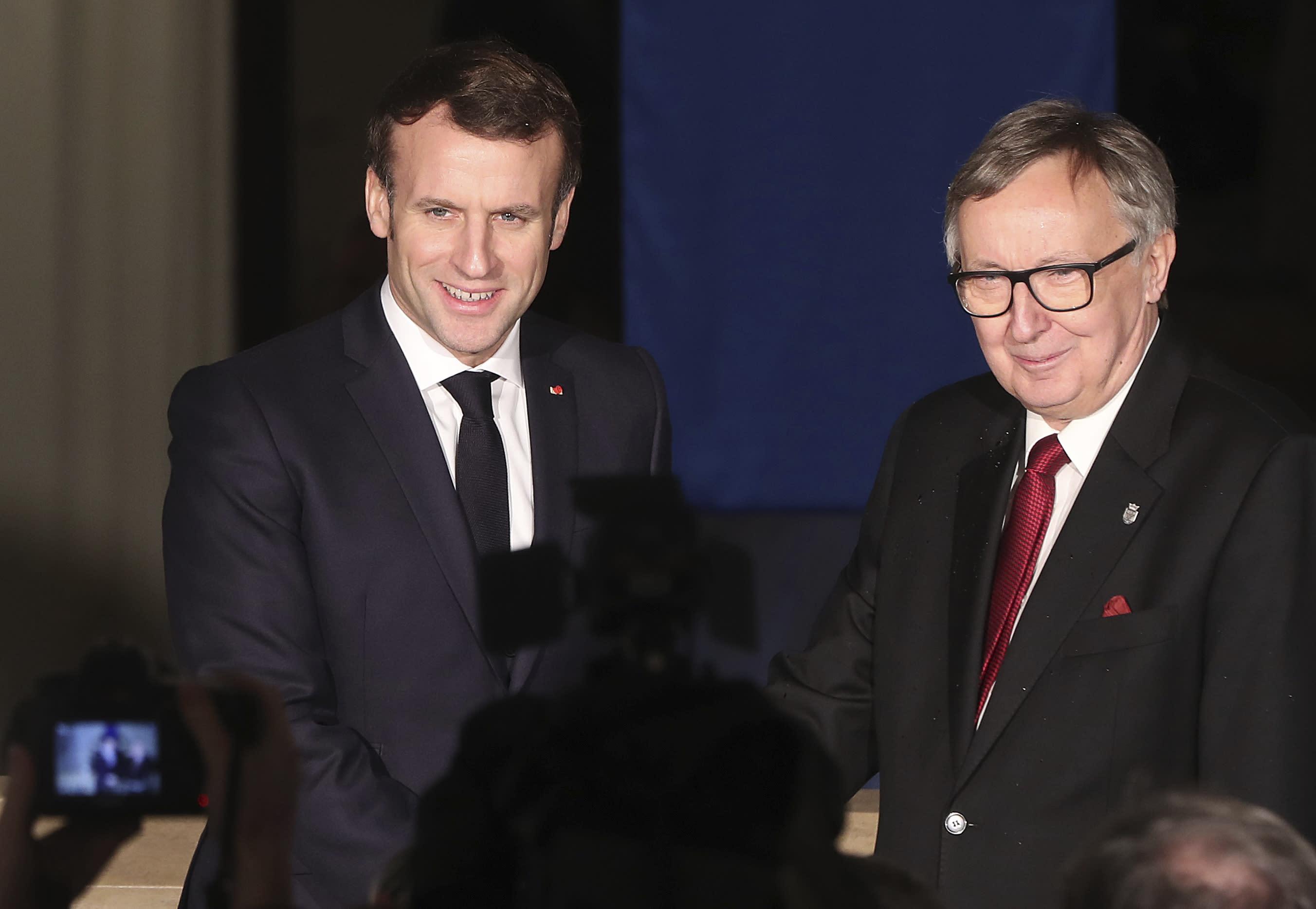 French President Emmanuel Macron, left, shakes hands with the rector of Jagellonne University, Wojciech Nowak, before giving a speech in Krakow, Poland, Tuesday, Feb. 4, 2020.(AP Photo/Czarek Sokolowski)