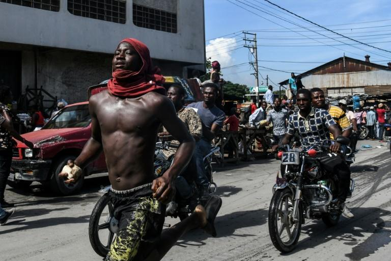 (FILES) In this file photo taken on September 23, 2019 demonstrators march on the street near parliament as they protest against ruling government in Port-au-Prince. The UN has called for calm in crisis-wracked Haiti, eight days before the end of its police mission (AFP Photo/CHANDAN KHANNA)